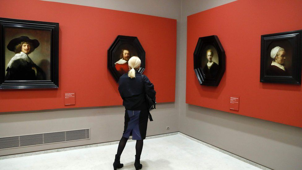 A woman looks at paintings by Dutch painter Rembrandt at the Louvre Museum on 17 February 2017