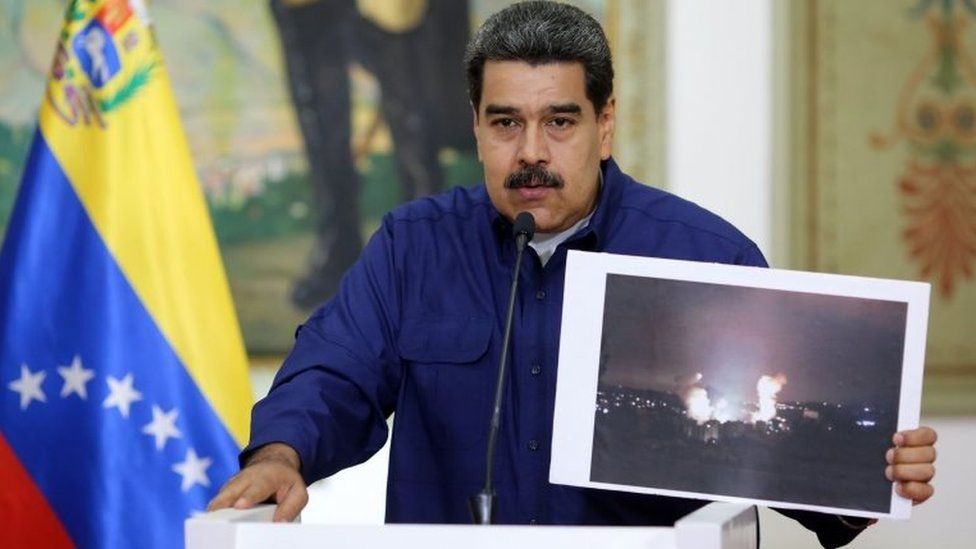 Handout picture released by the Venezuelan presidency showing Venezuelan President Nicolas Maduro showing a picture of the fire at a state-owned electricity company Carpooled power substation, during a press conference at the Miraflores Presidential Palace in Caracas, Venezuela on March 11, 2019