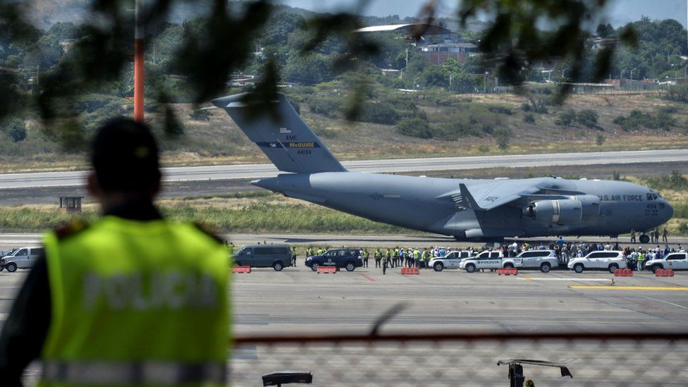A Colombian police officer stands guard as a US Air Force C-17 aircraft carrying food and medicine for Venezuela arrives at the Camilo Daza International Airport in Cucuta, Colombia, 16 February 2019