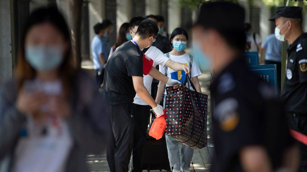 Students have their bags disinfected before entering Wuhan University, on the first day of classes in Wuhan on June 8, 2020