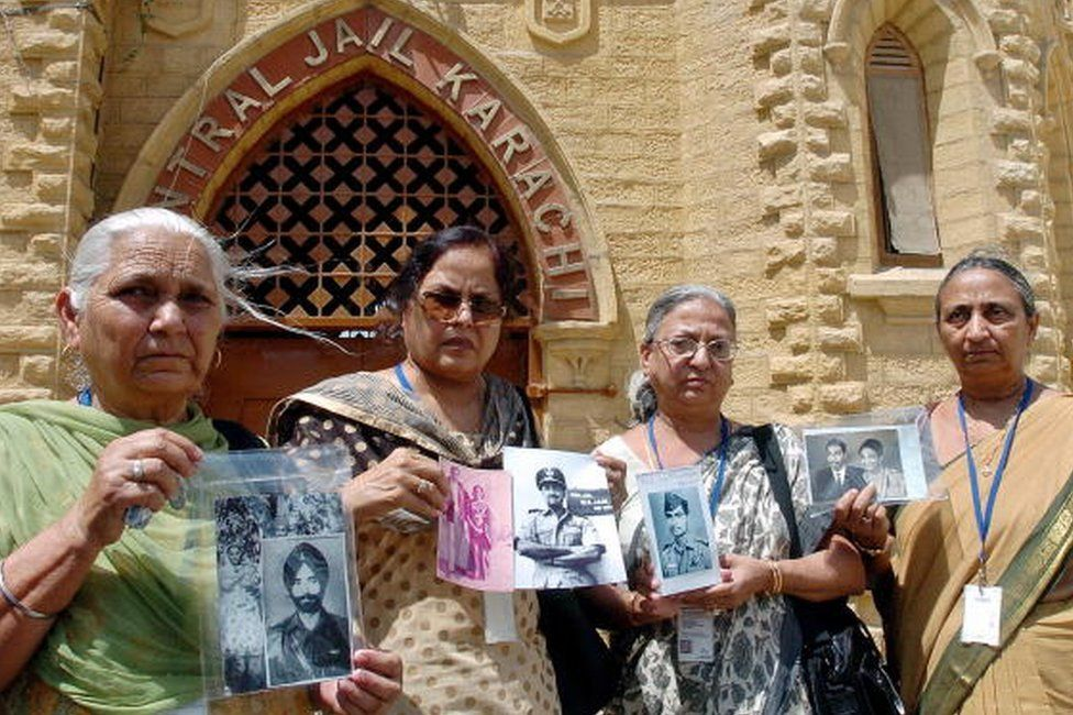 Members of an Indian delegation show pictures of missing Prisoner of War (POW) relatives during a tour of the central jail of Karachi, 04 June 2007