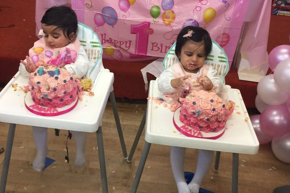 Twins sitting in highchairs eating a cake each