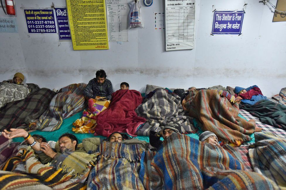 People sleep in a night shelter on a cold winter night at Jama Masjid, on December 28, 2019 in New Delhi, India.