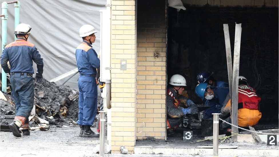 Investigators inspect the scene of the fire at Kyoto Animation