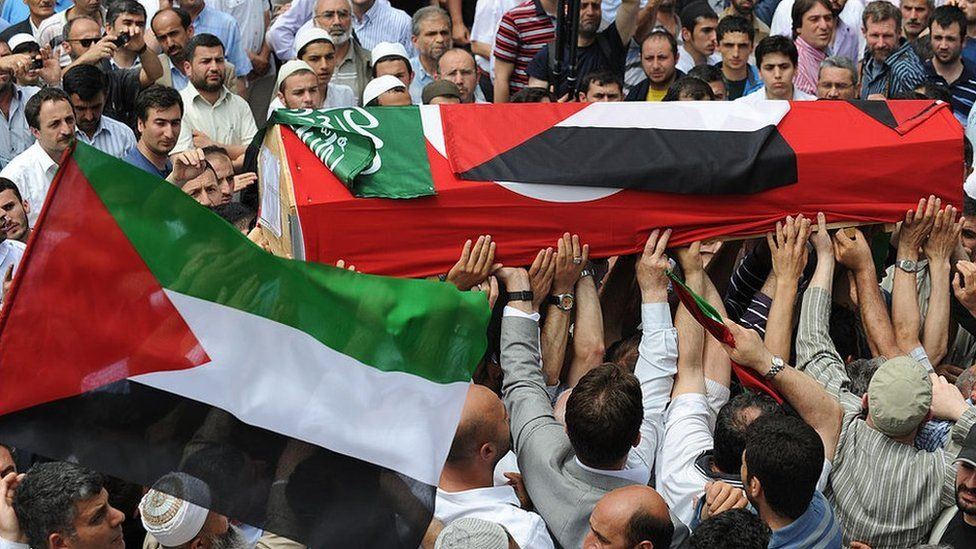 A coffin draped in a Turkish and a Palestinian flag is carried along during a funeral service for activists killed on Mavi Marmara, in Istanbul on 3 June 2010