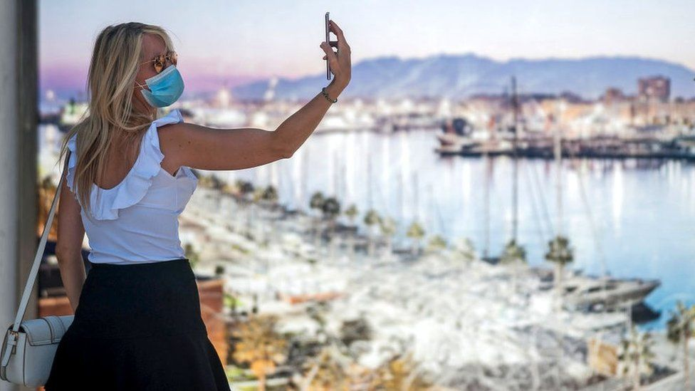 Woman taking a selfie wearing a face mask in Malaga.