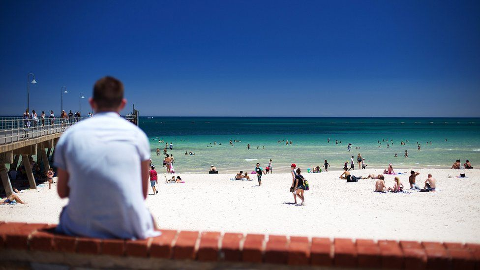 People enjoy Adelaide's Glenelg beach amid a heatwave earlier this month