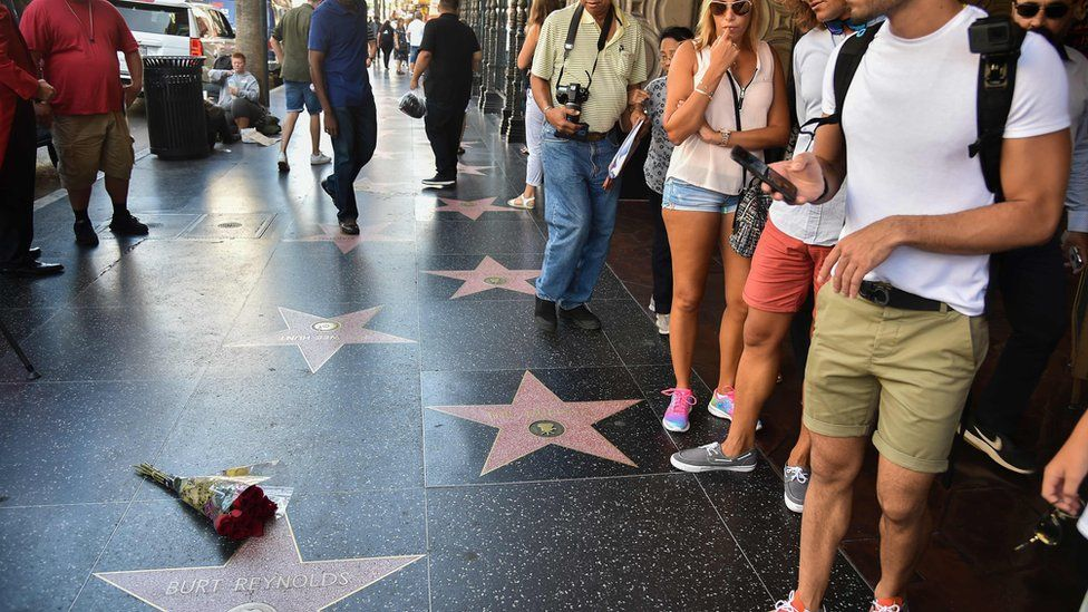 Tourists stand near flowers placed on the star of actor Burt Reynolds on the Hollywood walk of fame in Hollywood