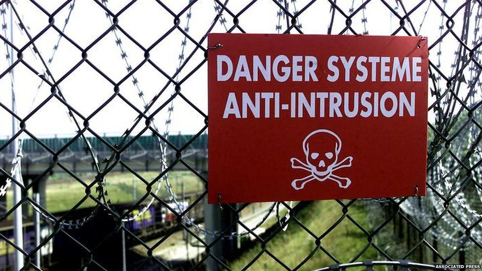A danger sign on the security fence at Sangatte