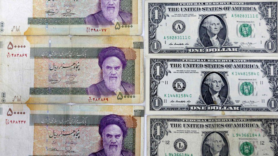 Close-up image of Iranian Rial banknotes and US one dollar bills