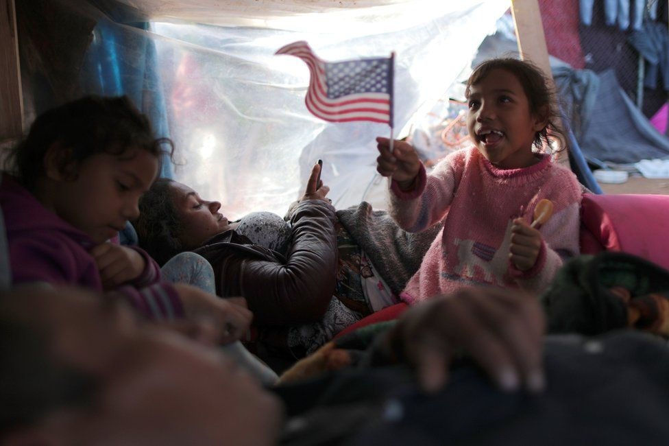 Jeyri, a seven-year-old migrant girl from Honduras, waves a US flag as she rests with her family in a temporary shelter in Tijuana, Mexico, 23 November