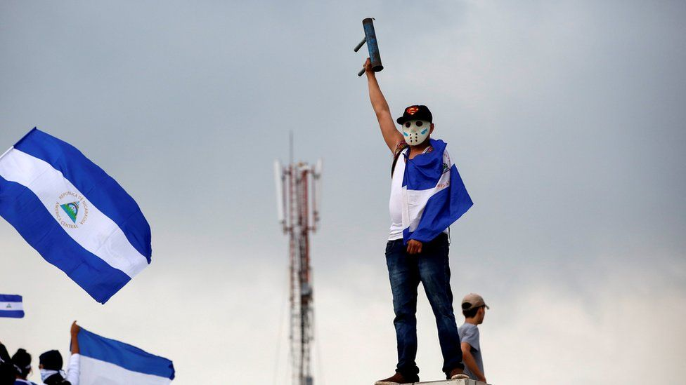 A man wearing a baseball cap, hockey mask, and draped in the national flag raises his home-made mortar in victorious salute in Managua, Nicaragua May 26, 2018.