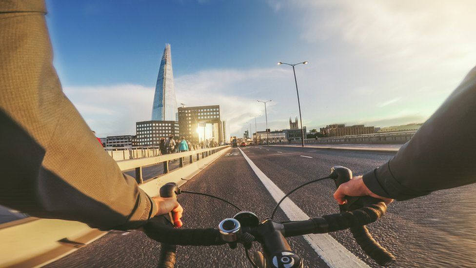 Someone cycling over a bridge in London