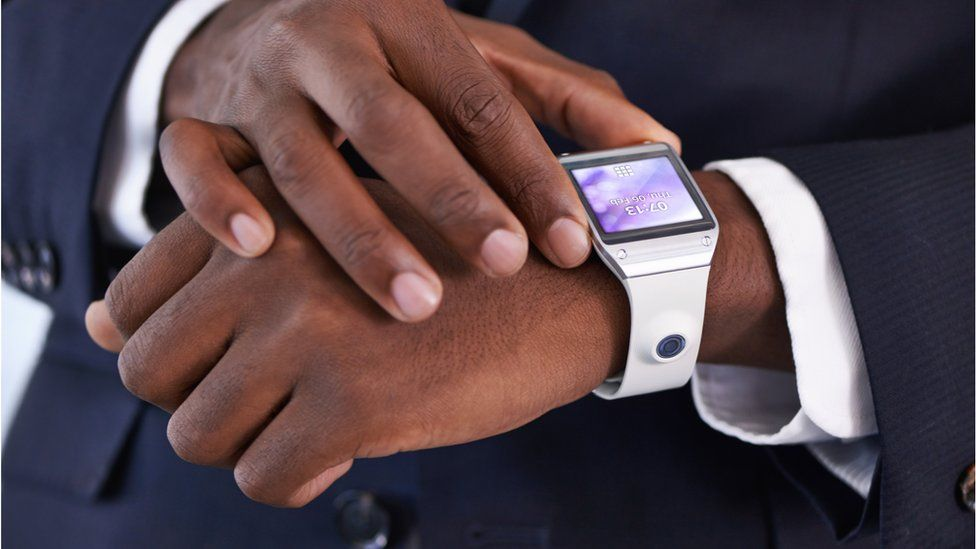 A man looking at a digital watch