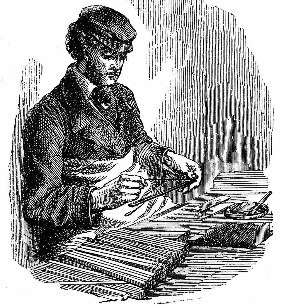A man inserts graphite between strips of cedarwood in an 1872 engraving