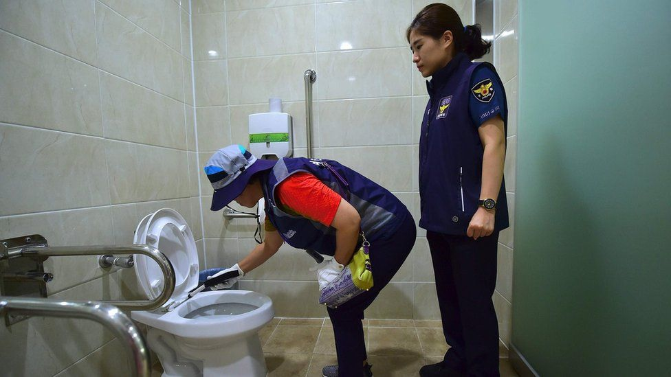 A member of Seoul's hidden camera hunting squad, and a police women, inspect a bathroom for spy cameras