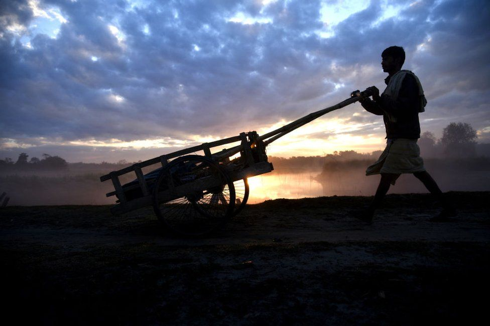 A man pushes his cart to go to work early in the morning during sunrise as clouds gather on the sky in the outskirt of Guwahati in Assam, India on Friday, December 21, 2018