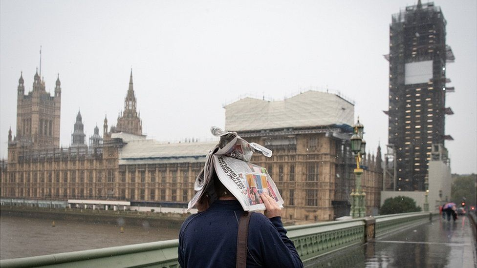 A pedestrian holds a newspaper over their head to shelter from rain near the Palace of Westminster