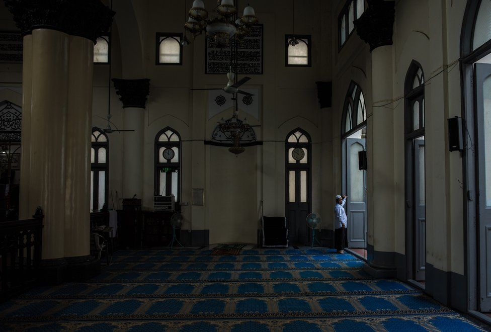 Farooq prepares the prayer room for Zuhr - just after midday - prayer, at the Shia Mughal Mosque in downtown Yangon, Myanmar, November 19, 2015