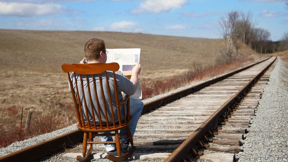 A man reads newspaper whilst sitting on a rocking chair placed on a railroad track