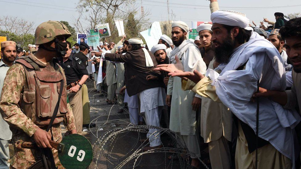 """Pakistani supporters of convicted murderer Mumtaz Qadri argue with soldiers during a protest against Qadri""""s execution in Peshawar on February 29, 2016."""