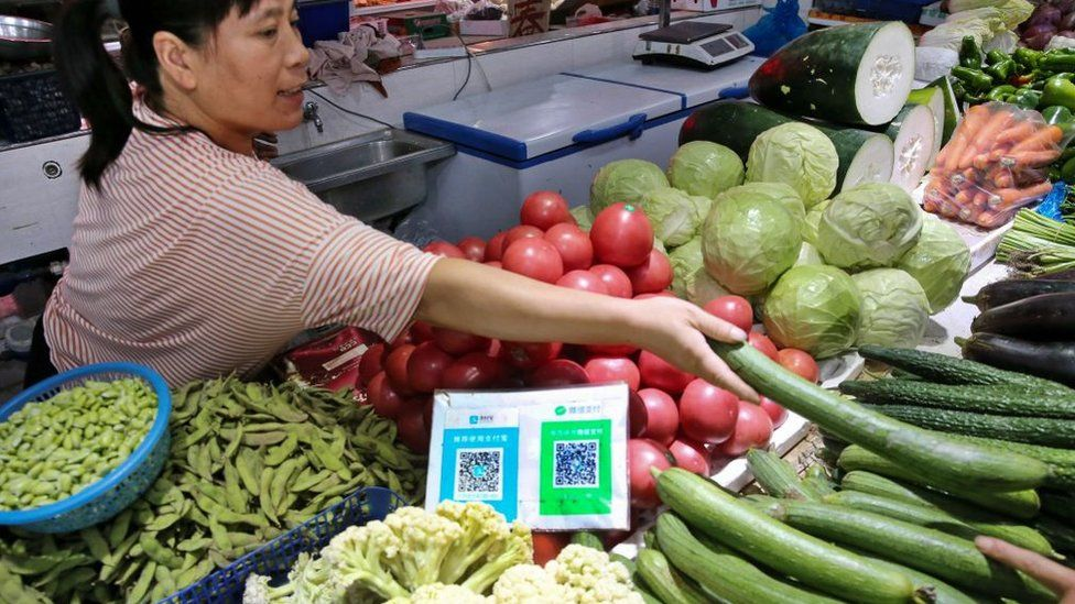 A woman sells fruit and vegetables in a Chinese market stall with a QR code on display