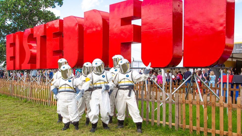 Eisteddfod sign with individuals dressed as astronauts in front of the sign