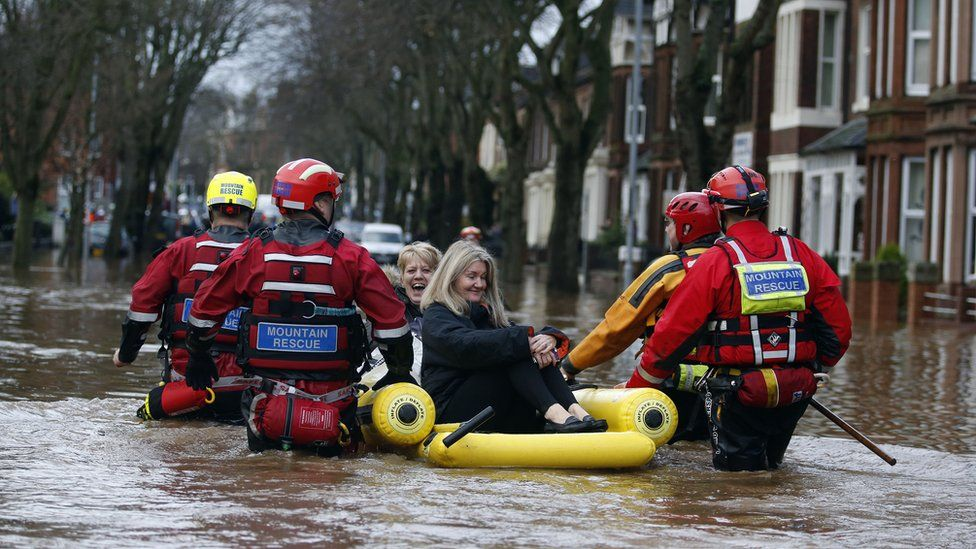 Emergency workers use an inflatable raft to rescue two women from flooding