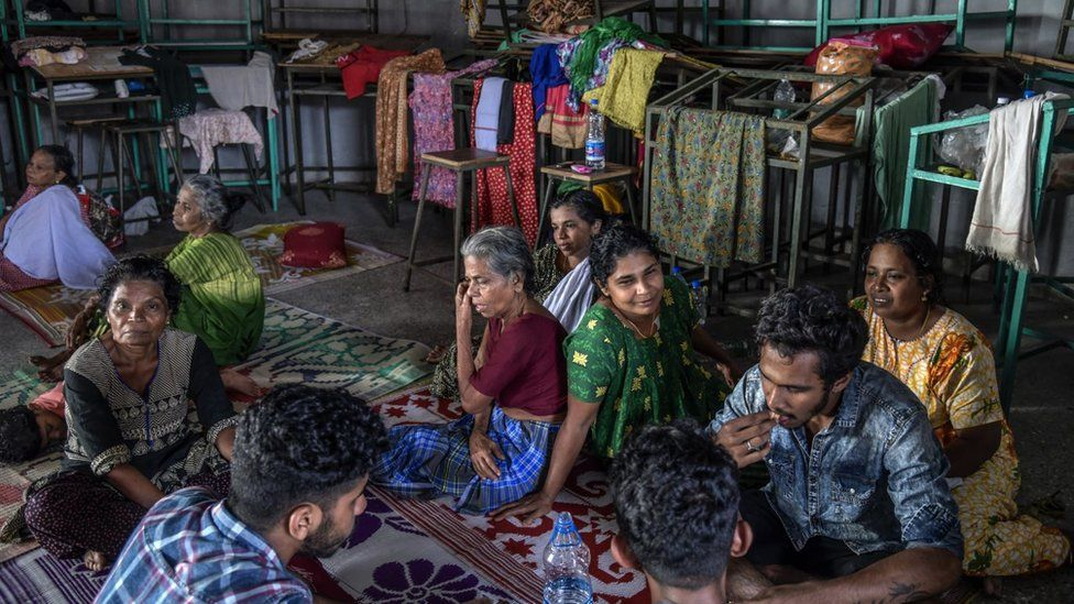 Women and men sitting in a refugee shelter