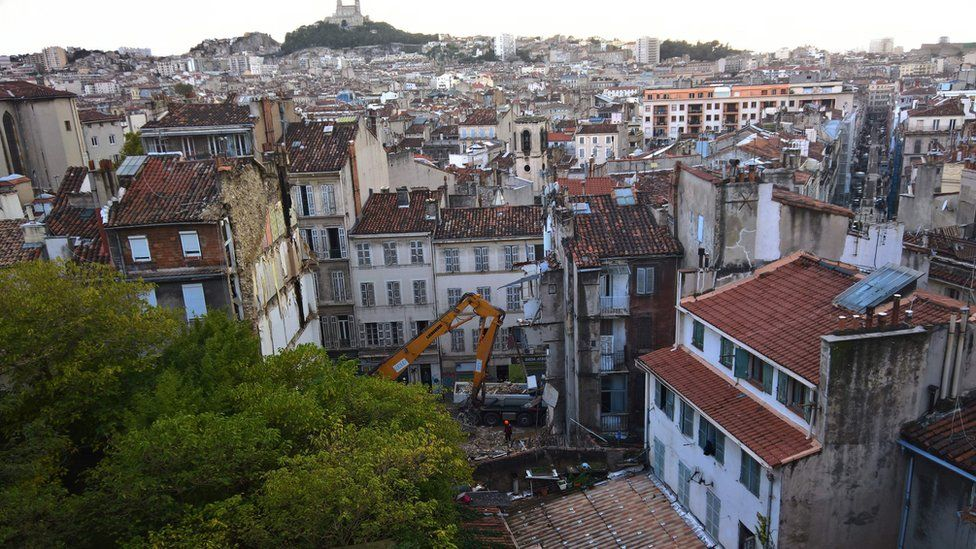 A view taken on November 6, 2018 from a neighbouring building shows workers removing rubble where two buildings collapsed, resulting in at least two people injured, in Marseille