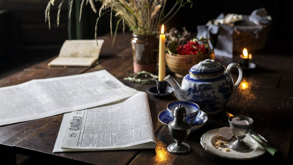 A newspaper lays open on a wooden table, next to a china teapot and cups