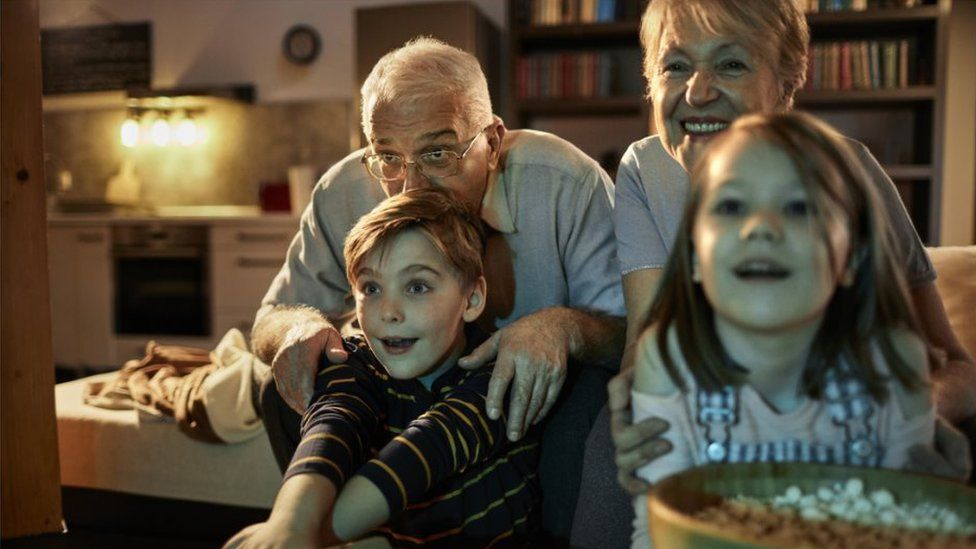 stock photo - Close up of grandparents watching a movie together with their grandchildren