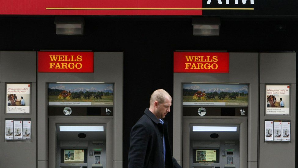 A man walks by Wells Fargo ATMs