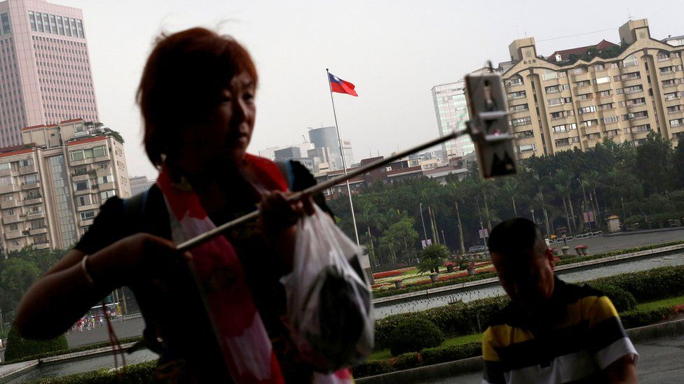 A tourist from China takes a selfie in front of a Taiwanese flag, in Taipei