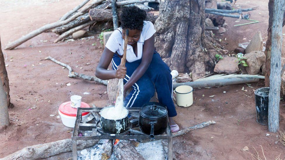 A woman cooks a typical dish, called Sadza (or Ugali, nshima, pap, phutu) on a saucepan and a fire pit