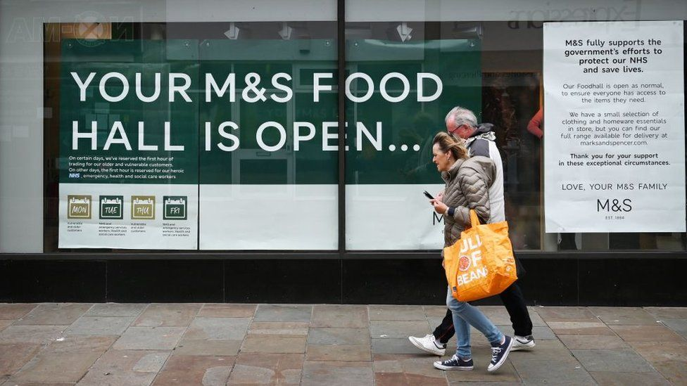 "Couple walk past sign saying: ""Your M&S food hall is open"""