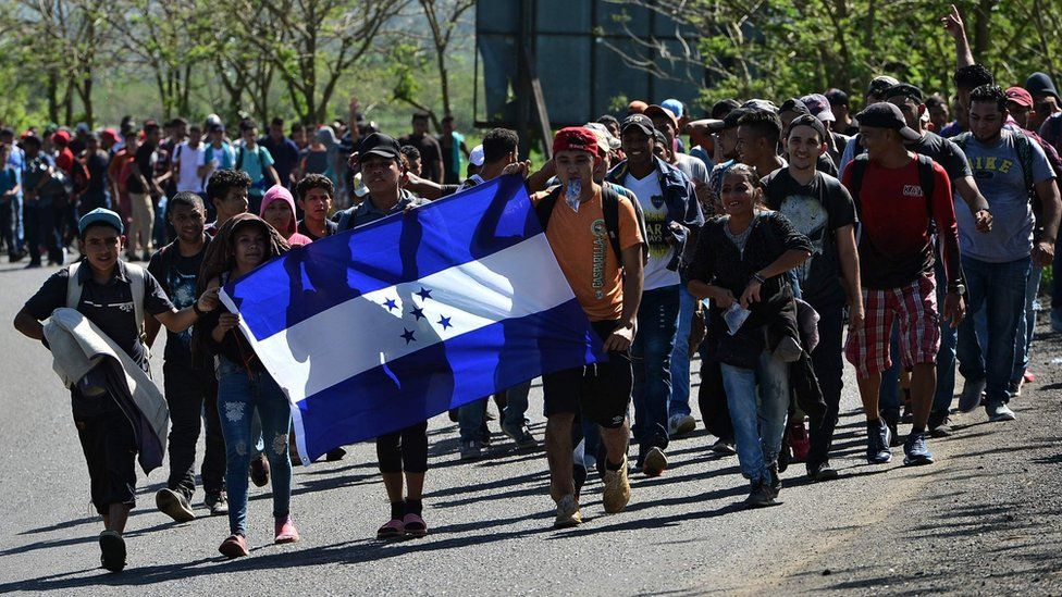 Honduran migrants walk with a Honduran national flag heading to Puerto Barrios, in Izabal department, Guatemala