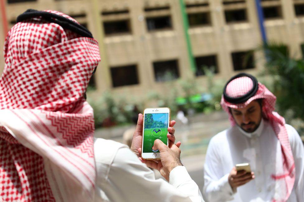 Men searching for Pokemon characters in Saudi Arabia
