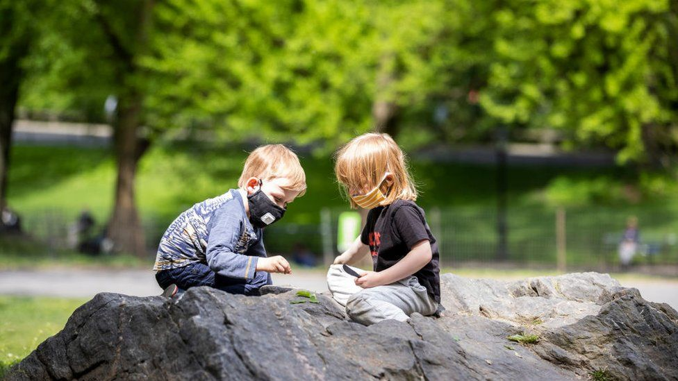 On Memorial Day weekend a two children wear a masks (personal protective equipment) while sitting on the rocks and playing with leaves in Central Park
