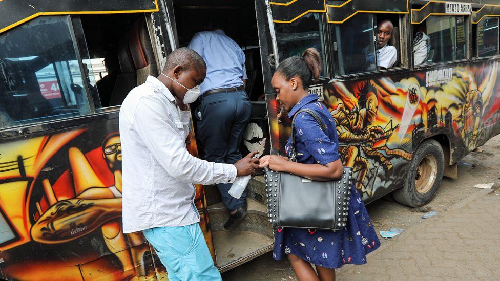A matutu minibus operator sprays a passenger's hands in Nairobi, Kenya - Friday 13 March 2020