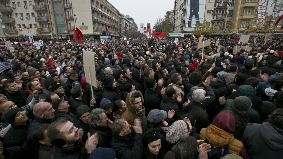 Kosovo policemen detain a man at the Vetevendosje headquarters after several thousand of supporters of opposition party gathered in downtown Pristina