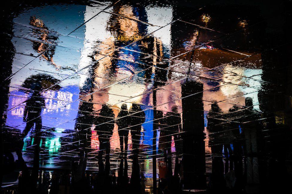 Rainy reflections of adverts.