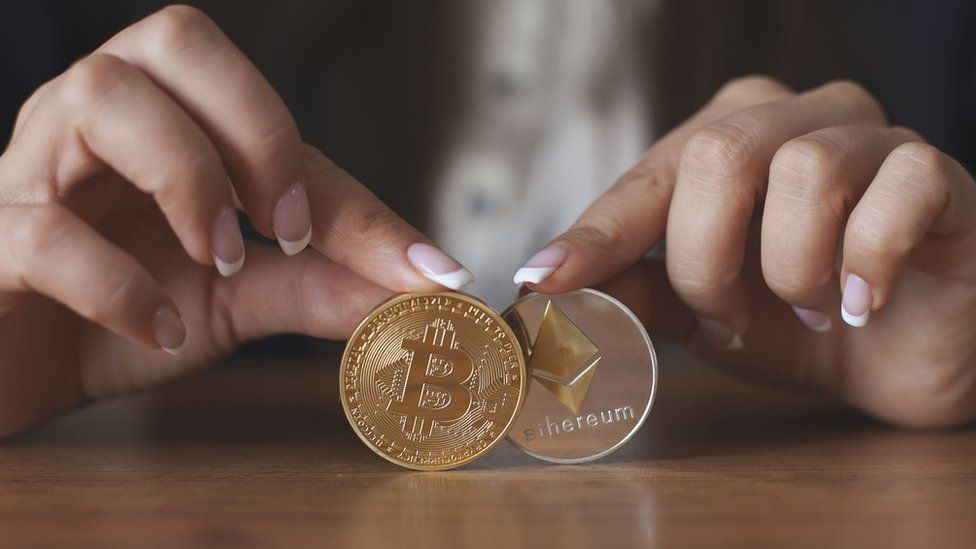 Woman holding Bitcoin and ethereum coins