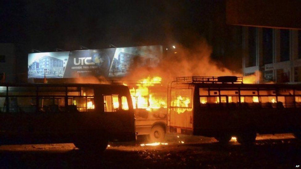 In this late Tuesday, Aug. 25, 2015 photo, passenger buses set on fire by a mob go up in flames in Surat, Gujarat state, India