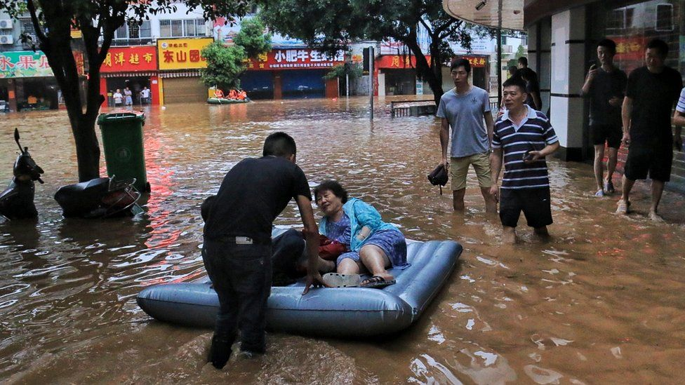 People wade in a flooded street on June 9, 2019 in Guilin, Guangxi