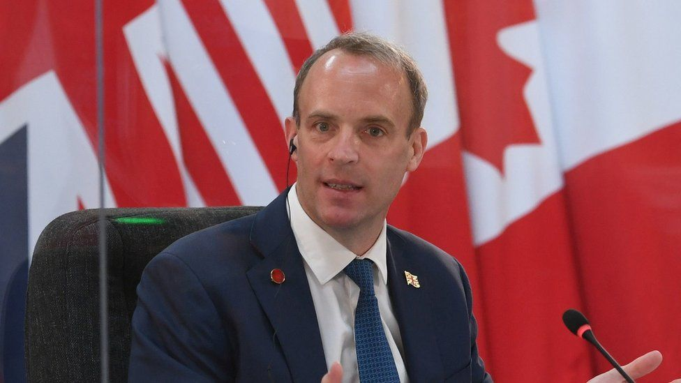 Dominic Raab delivers an address seated before a range of flags
