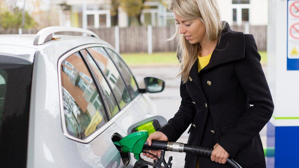 woman filling car with fuel