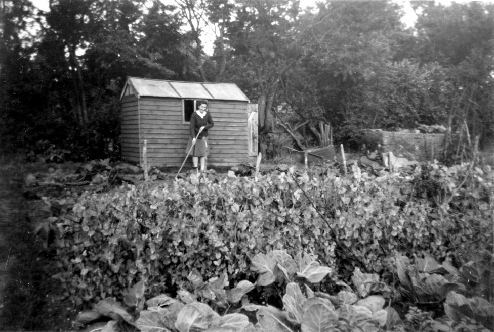 Eileen Newell in front of a garden shed