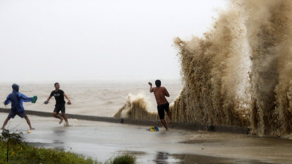 Residents play in waves in Aparri, Cagayan province, after Typhoon Mangkhut, 15 September 2018