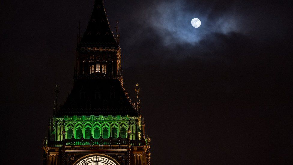 The Ayrton light shining at the top of Elizabeth Tower